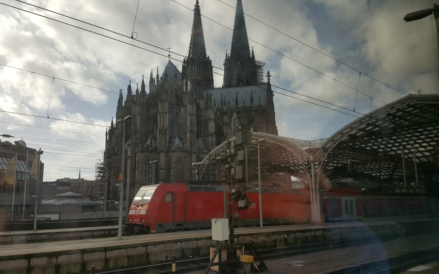 Andreas reflected in the train window pulling into the station in Cologne. Photo by Dragonfly Leathrum