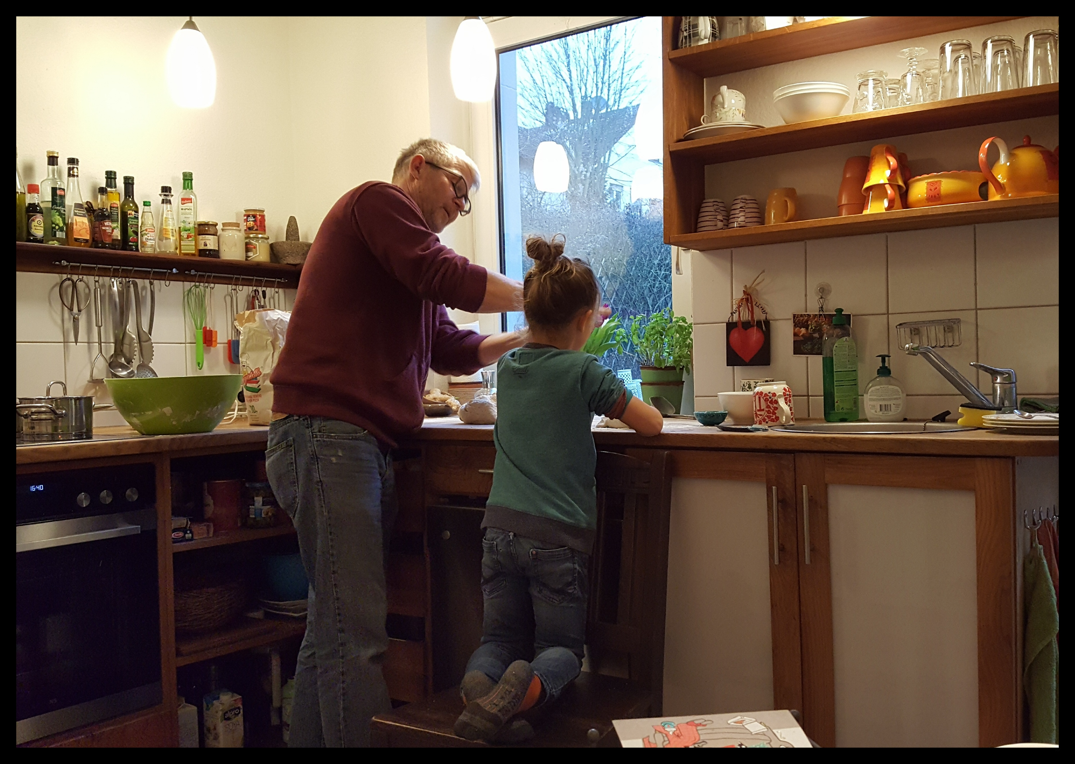 Burkhard's neighbor friend gets a lesson in pizza dough making before the party. Photo by Dragonfly Leathrum