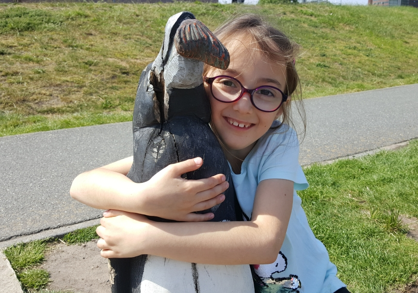 Playground by the zoo. This girl loves all animals, even if they're wooden statues. Photo by Dragonfly Leathrum