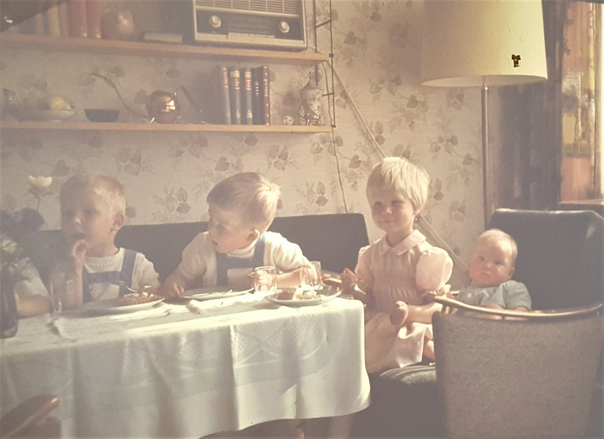 Cuties at the kids table From left to right: Burkhard, Andreas, cousin Petra and baby Christina. Photo taken on Wikinger Str. in Leck, Germany early 1965. This photo taken from the slide projected on the wall.
