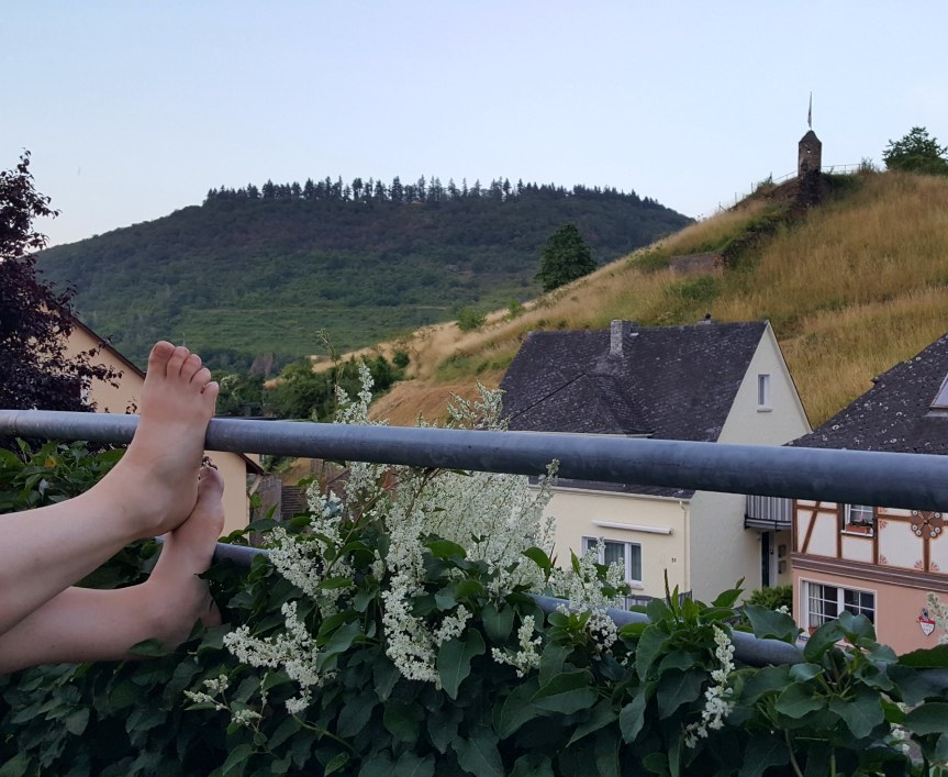 Andreas enjoying the late evening (9:45pm) breezes on our balcony while watching women's World Cup soccer. The castle is up the hill to the right. Photo by Dragonfly Leathrum