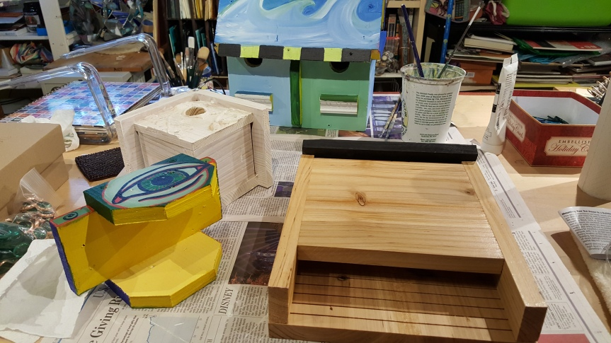 Bat and birdhouses in progress using acrylic paint. Photo by Dragonfly Leathrum