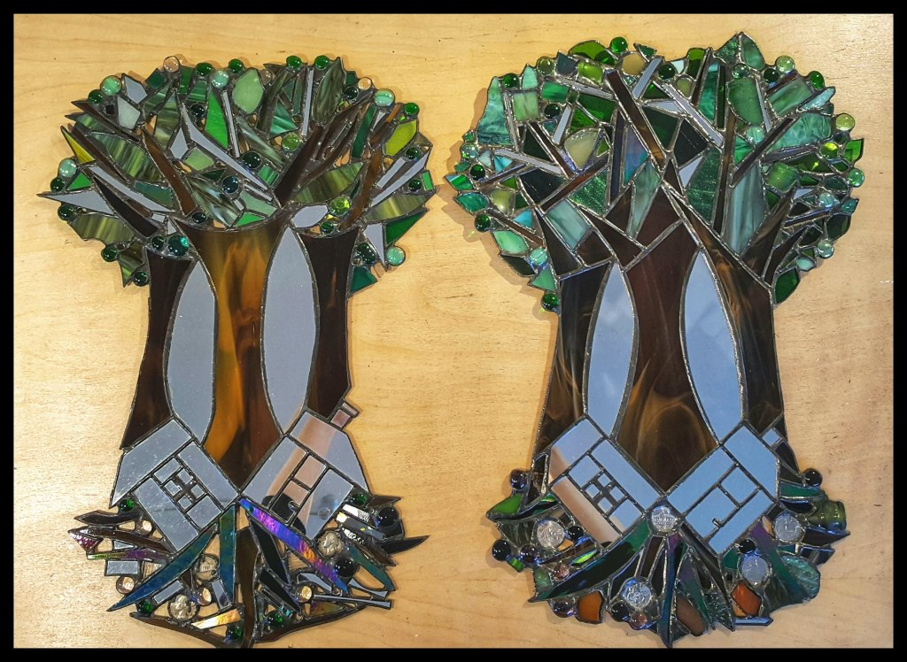 Plant Trees Not Houses, original on the left created in 1998, new and improved 2021 on right. Stained glass and photo by Dragonfly Leathrum